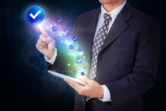 Businessman holding tablet with pressing check mark icon button. Internet and technology concept stock photography