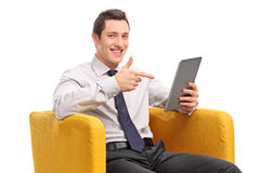 Businessman holding a tablet seated in an armchair Stock Photography
