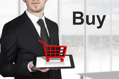 Businessman holding tablet shopping cart buy Stock Image