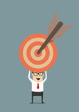 Businessman holding target with arrow Stock Photo