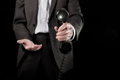 Businessman holding telephone handset Stock Images