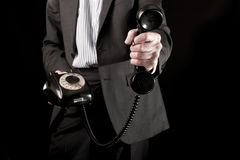 Businessman holding telephone handset Stock Photos
