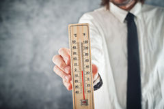 Businessman holding thermometer with temperature on Zero value Stock Photo