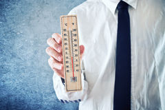 Businessman holding thermometer with temperature on Zero value Royalty Free Stock Photography