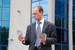 Businessman holding three CD/DVDs Stock Images