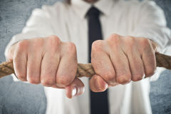 Businessman holding tight to a rope. Concept of business problems, difficult business situation Stock Image