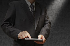 Businessman holding a touchpad. On dark Royalty Free Stock Photo