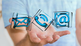 Businessman holding transparent cube contact icon in his hand 3D. Businessman on blurred background holding transparent cube contact icon in his hand 3D Stock Images