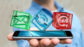 Businessman holding transparent cube contact icon over phone, 3D. Businessman on blurred background holding transparent cube contact icon over phone 3D rendering Stock Image