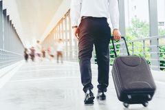 Businessman holding trolley bag going up on travel.  Royalty Free Stock Images
