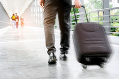 Businessman holding trolley bag going up on travel.  Royalty Free Stock Photography