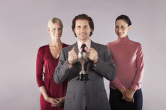 Businessman Holding Trophy With Female Colleagues Royalty Free Stock Photo