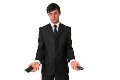 Businessman holding two mobile phones. Isolated on white background Stock Photos