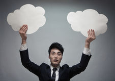 Businessman holding two paper clouds, studio shot Stock Photos