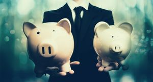 Businessman holding two piggy banks. On blue abstract light background Royalty Free Stock Image
