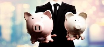 Businessman holding two piggy banks. On pink and blue abstract light background Royalty Free Stock Photos