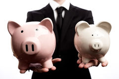Businessman holding two piggy banks. On a white background Stock Image