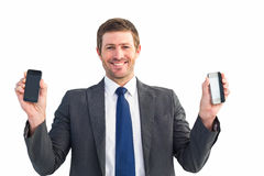 Businessman holding two smart phones Royalty Free Stock Images