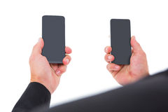Businessman holding two smart phones Royalty Free Stock Photography