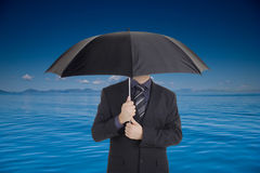 Businessman holding an umbrella Stock Photos