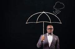 Businessman holding an umbrella. royalty free stock image