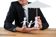 Businessman holding an umbrella protecting a family Royalty Free Stock Image