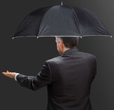 Businessman holding umbrella and reaching hand out Royalty Free Stock Images