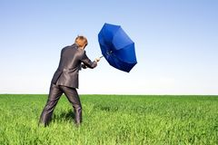 Businessman holding an umbrella in a storm. Stock Photo