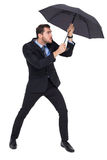 Businessman holding umbrella to protect himself Royalty Free Stock Photo