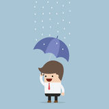 Businessman holding an umbrella under the rain Royalty Free Stock Photos