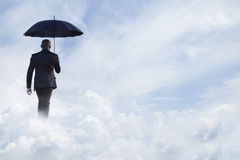Businessman holding an umbrella and walking  away in dreamlike clouds Royalty Free Stock Photos