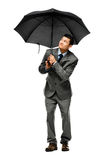 Businessman holding umbrella Royalty Free Stock Photos