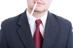 Businessman holding an unlit cigarette between lips Royalty Free Stock Photography