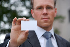 Businessman holding up businesscard Royalty Free Stock Image