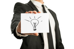Businessman holding up a card with conceptual light bulb drawing Royalty Free Stock Photo