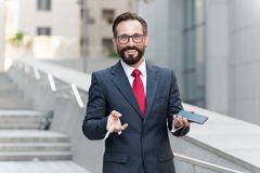 Businessman holding up credit card and making online payment on his cellphone with building background. A businessman holding up credit card and making online Royalty Free Stock Image