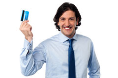Businessman holding up his credit card Stock Photos