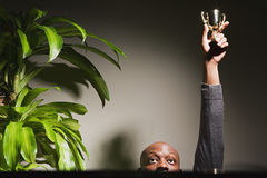 Businessman holding up his trophy Royalty Free Stock Photography