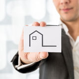 Businessman holding up a house icon on a card Royalty Free Stock Image