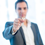 Businessman holding up a key Stock Image