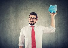 Businessman holding up a piggy bank. Finance and savings concept royalty free stock photo