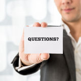 Businessman holding up a small white card saying Questions. In a conceptual image of customer support and client services, close up of his hand Stock Photography