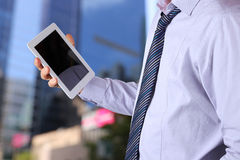 Businessman holding  and using the digital tablet. Modern city b Royalty Free Stock Photos
