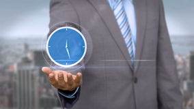 Businessman holding virtual alarm clock. With city on background stock footage