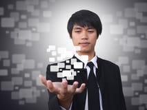 Businessman holding virtual button Stock Photo