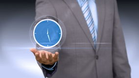 A businessman holding virtual clock. On grey background stock footage