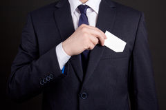 Businessman holding visiting card out of his suit pocket Royalty Free Stock Images