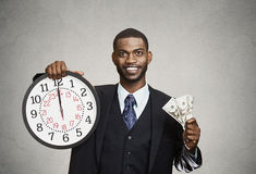 Businessman holding wall clock and cash in hands. Time is money. Closeup portrait happy young business man, corporate employee, ceo, holding wall clock, dollar stock images