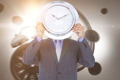 Composite image of businessman holding wall clock in front of face Royalty Free Stock Images