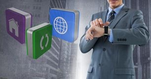 Businessman holding watch with apps icons with city background Royalty Free Stock Images